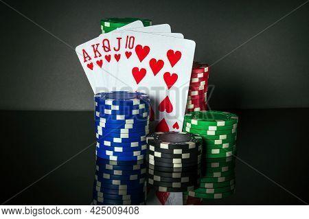 Poker Cards With Troyal Flush Combination. Close-up Of Playing Cards And Chips In Poker Club