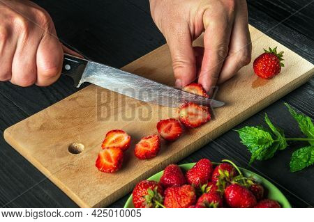 Close-up Chef Hands Cut Fresh Strawberries On Cutting Board Of Restaurant Kitchen For Making Soft Dr