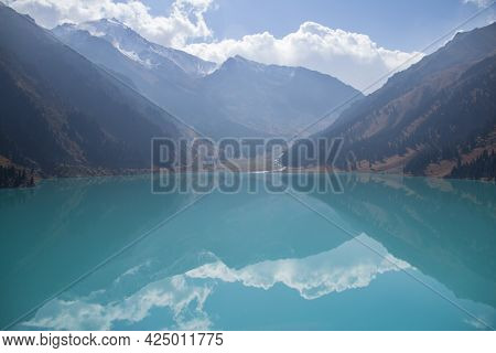 Mirror Of The Big Almaty Lake With Reflection High In The Mountains With Snow-capped Peaks And A Sky