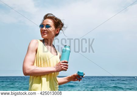 Young Sporty Woman Dressed In Sporty Clothes Drinks Water From Steel Thermal Bottle On The Beach Aft