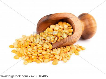 Dry Yellow Split Peas In Wooden Scoop, Isolated On White Background. Halves Of Yellow Legume Peas.