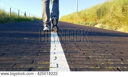 Man Walking Asphalt Road, Backview Of Person Taking A Walk On The Middle Of A Road, Legs And Shoes