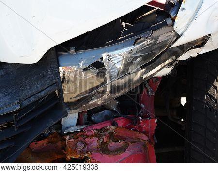 A Fragment Of A Car With A Broken Headlight And A Dented Rusty Bumper. Car After An Accident. Closeu