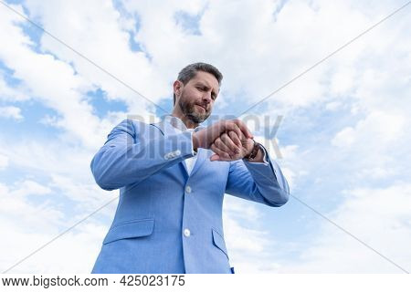 Handsome Mature Man Businessman In Formal Suit Check Time On Wristwatch On Sky Background, Deadline