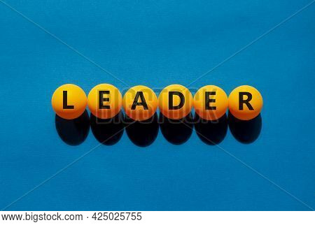 Leader And Business Symbol. The Concept Word 'leader' On Orange Table Tennis Balls On A Beautiful Bl