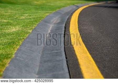 Curve Drainage Channel Cement Hollow Made Of Concrete On The Side Of An Asphalt Road With Yellow Mar