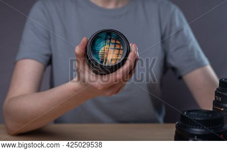 Digital Camera Lens With Beautiful Studio Softbox Reflecting In Hands Of Female Photographer Over De