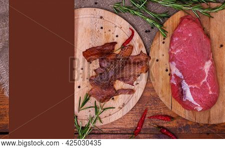 Jerky Meat And Raw Beef On Circle Wooden Boards On Brown Background With Copy Space. Ingredients For