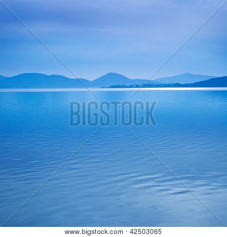 Water surface in a blue morning on the Trasimeno lake Umbria Italy. Hills on background. Long exposure photography in Lido Camaiore Versilia Tuscany Italy Europe poster