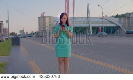 Young Woman On City Roadside With Smartphones In Hand. Casual Brunettein In A Turquoise Dress On Pav