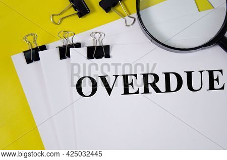 Overdue Word Written On White Paper And Yellow Background With Magnifier