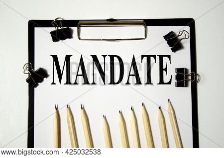Mandate The Word Is Written On A White Piece Of Paper With Pencils