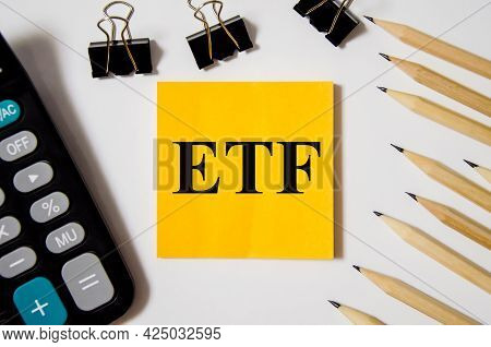 Exchange Traded Funds Word Is Written On A Yellow Piece Of Paper On A White Background Near A Calcul