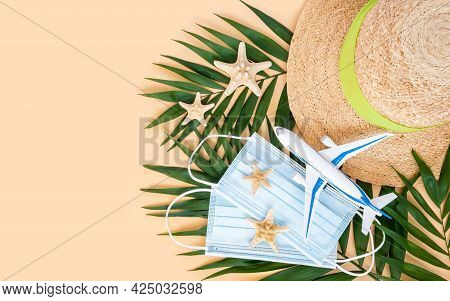 Summer Hat, Plane, Medical Mask And Sea Stars On Palm Leaf On Neutral Beige Background. Travel And H