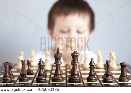 A Chessboard With Spaced Figures, In The Background A Boy Out Of Focus. Board Game Of Chess. Tournam