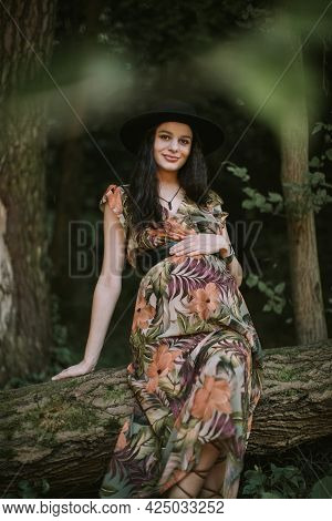 Pregnant Likable Caucasian Woman 25-30 Year Old Wearing Colorful Dress And Black Hat Posing Outdoors