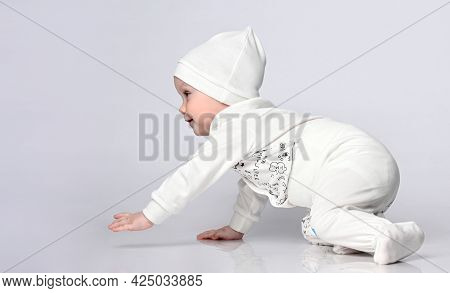 Side View Of A Pretty 10-month Toddler Crawling In The Light Body And Panties In A Nice Hat.