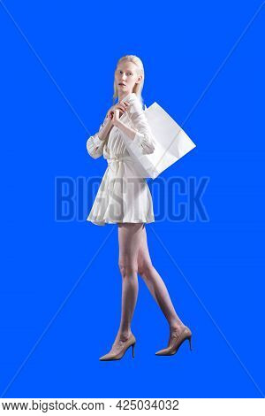 White Caucasian Albino Blond Woman Holds Shopping Bag On Isolated Blue Background. Sale And Discount