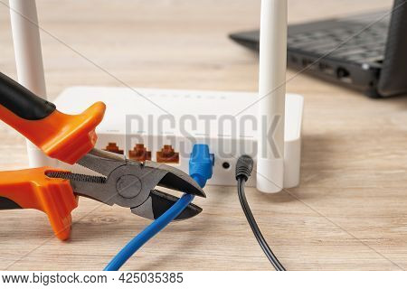 Close-up Of Wire Cutters Ready To Cut The Network Cable Connected To White Wi-fi Wireless Router On