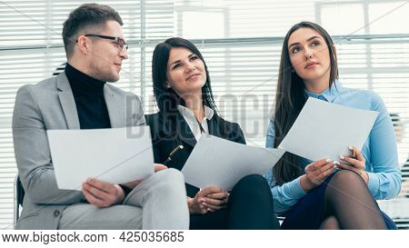 Close Up. A Group Of Employees Discussing The Questionnaire For The Interview