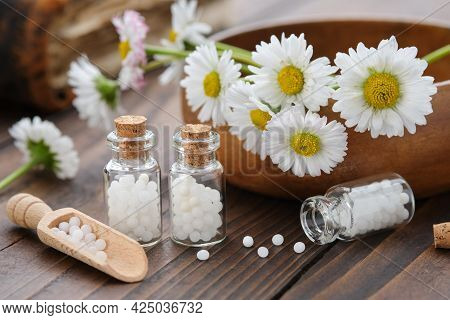 Bottles Of Homeopathy Granules. Homeopathic Remedy - Chamomilla. Daisies Flowers In Wooden Bowl. Hom