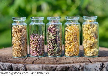 Glass Bottles Of Medicinal Herbs - Daisies, Heather, Wild Marjoram,  Calendula, Helichrysum Outside.