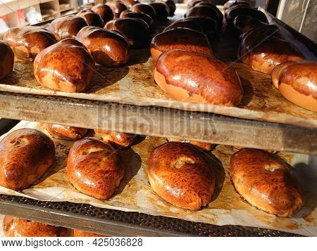 Close-up Of Many Hot Delicious Pies On Shelves In Bakery, Store. Production Of Bakery Products. Shel