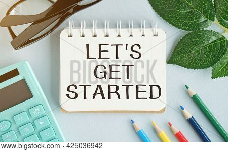 Let's Get Started Text Concept Write On Notebook With Office Tools On Blue Background