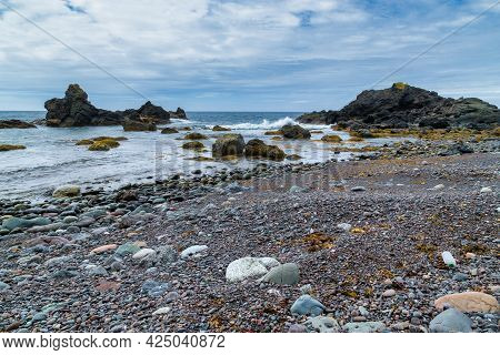 A Rocky Beach, With Mossy Rocks, Along An Ocean Shoreline - Gros Morne, Newfoundland, Canada.