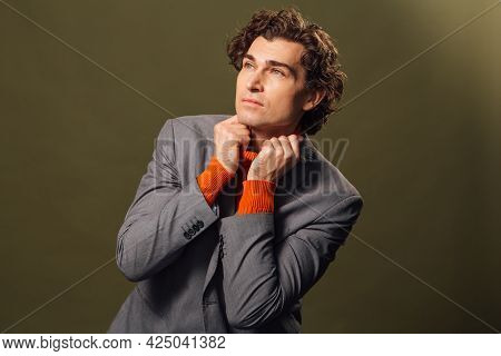 Tall Handsome Man Dressed In Orange Turtleneck, Grey Jacket And White Jeans Posing On The Green Back