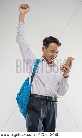A Boy Wearing A Junior High School Uniform Looking At A Phone With Raised Hand An Excited Gesture