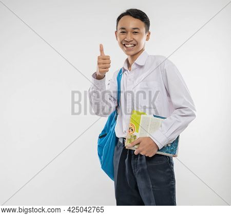 A Smiling Boy Wears A School Uniform And Carries A Backpack And Book With Thumbs Up To The Camera
