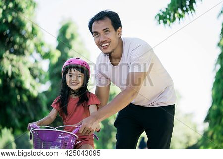 Father Teaching Daughter To Ride Bike In The Park