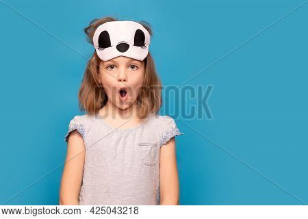 Portrait Of Young Girl With Surprised Face And Sleeping Mask On Head Isolated Over Blue Background.