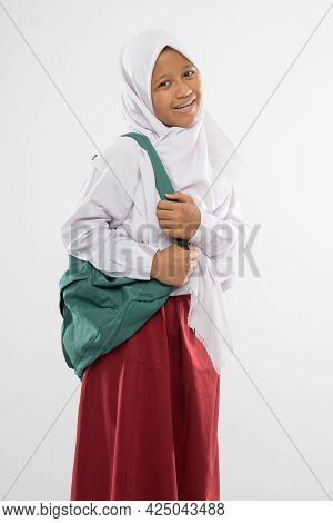 A Smiling Girl Wearing A Veiled Elementary School Uniform With A School Bag
