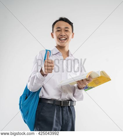 A Boy Wearing A Junior High School Uniform Smiles While Holding A Book With Thumbs Up