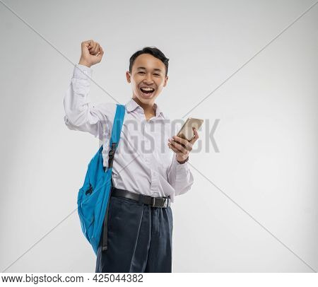 A Boy Wearing A Junior High School Uniform Smiled Happily While Holding A Cellphone With Raise Hand