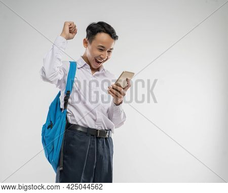 A Boy Wearing A Junior High School Uniform Looking At A Cellphone With An Excited Gesture With A Bac