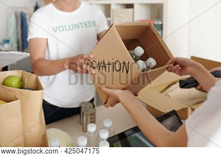 Person Donating Bottled Water To Charity Enter And Giving Box To Volunteer