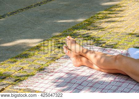Naked Legs Of A Woman Sunbathing Lying On A Blanket In A City Park On A Summer Day. The Rays Of The