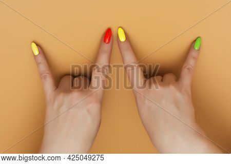 Beautiful Young Woman Hands With Summer Different Color Nail On Pastel Peach Background. Stylish Tre