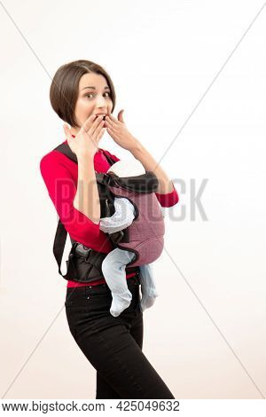 Babywearing Attractive Young Mother With Baby In Wrong Carrier. Isolated On White.