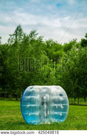 Blue Zorbing Balloon On The Summer Lawn. Inflatable Zorb Ball Outdoor. Leisure Activity Concept With