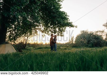 Love Story A Guy With A Girl Kissing In The Forest. Loving Married Couple On A Romantic Date In The