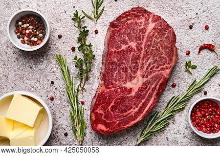 Fresh Marbled Beef Rib Eye Steak, Butter And On Grey Stone Background, Close-up