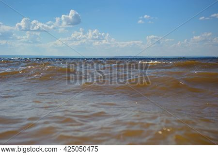Blue Sky And Airy White Clouds Float Over The Sea In Sunny Weather. Idyllic Clean Landscape. There A