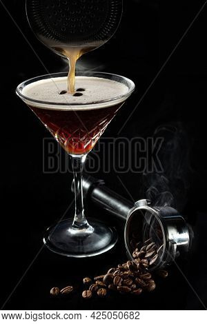 Alcohol cocktail Espresso Martini cocktails garnished with coffee beans, beans in espresso holder in smoke and on black background