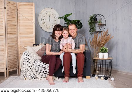 Family And Parenthood Concept - Portrait Of Happy Young Parents And Their Cute Little Daughter Havin
