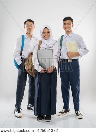 Two Boys And A Veiled Girl In Junior High School Uniforms Stand Smiling Carrying A Laptop Computer,