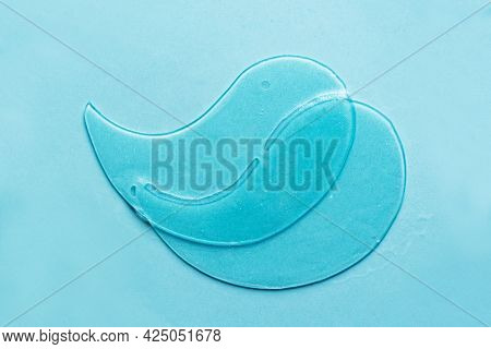 Hydrogel Blue Eye Patches On Blue Background Close Up. Cosmetic Moisturizing Under Eye Patches With